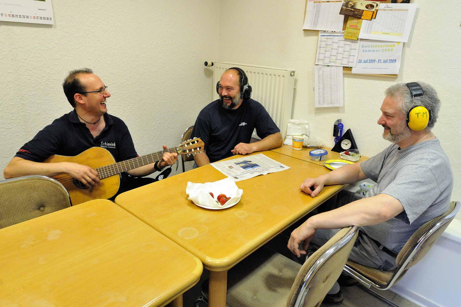 ein Ständchen darf es sein: der Meister spielt gerne Gitarre. Kollegen 'hören' zu.