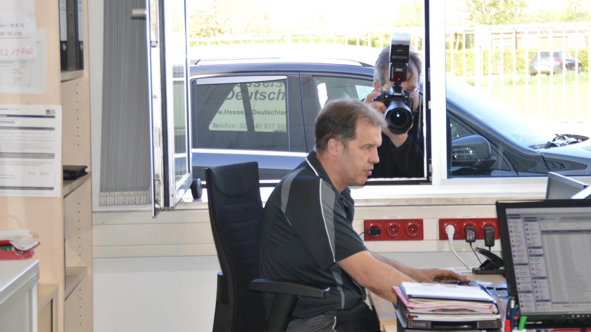 Making-of: Andreas Mann fotografiert hier das Motiv SERVICE BERATUNG. Der Aufsteckbitz löst den Blitz im Büro aus.