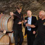 (v. l. n. r.): Tim Lilienström (Gutsverwalter), Peter Winter (Inhaber) und Ludwik Rebilas (Mitarbeiter Weinbau) im Weinkeller.