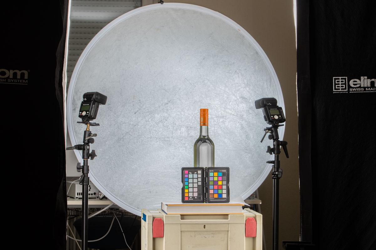 Weinflaschen mit Farbtafel und zwei große Flächenlichter. 2 Systemblitze leuchten den Hintergrund aus.